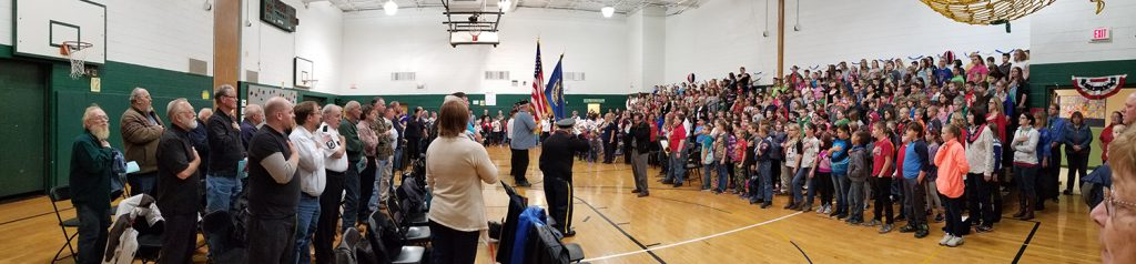 veterans and students stand for a flag ceremony