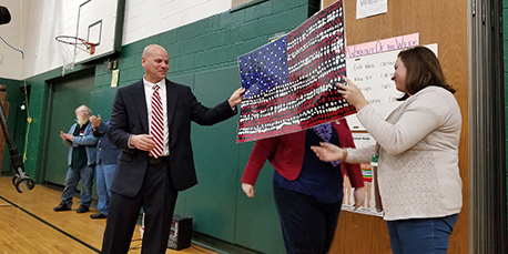 principal michael teator receives a painted american flag