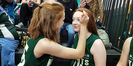 a student paints another student's face at the pep rally