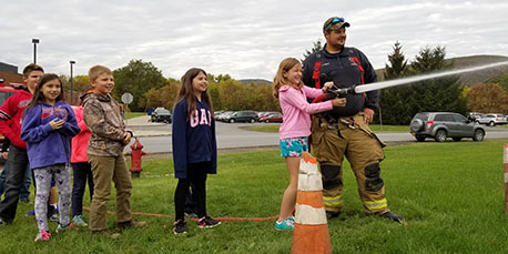 a student operates a hose while other students look on