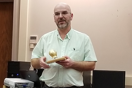 scott gray poses with his golden knight award