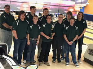 the boys varsity bowling team poses with their trophy