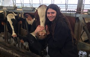 a student poses for a picture with a cow
