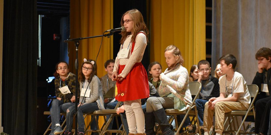a student spells a word during the district spelling bee