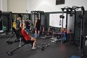 students use the equipment in the weight room