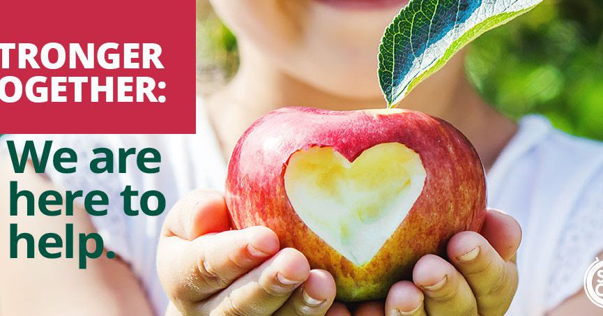 Child holding apple with a bite taken out of it in the shape of a heart. It also has the words, Stronger Together: We are here to help