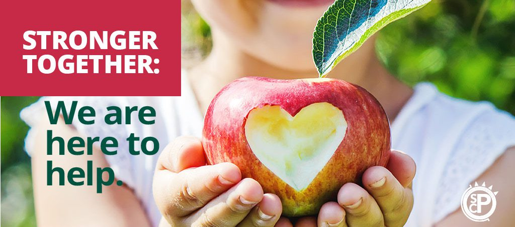 Child holds apple with a bite mark in the shape of a heart. It says, Stronger Together: We are here to help