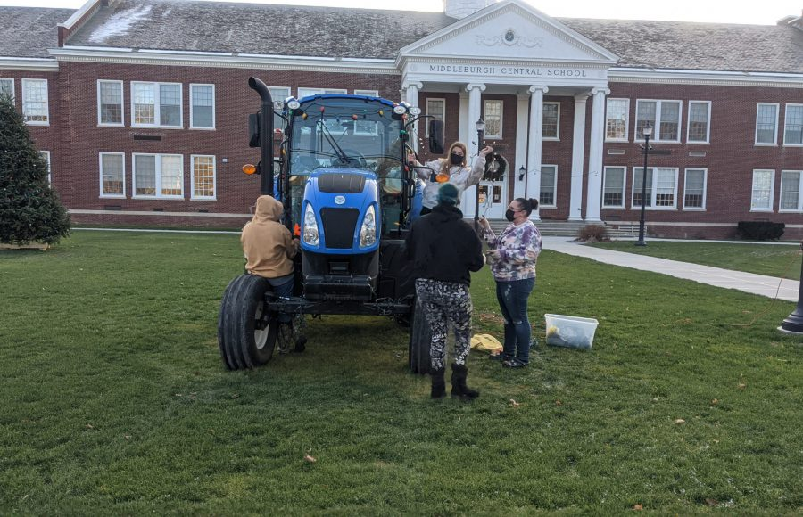 FFA officers decorating a tractor with lights for the holidays