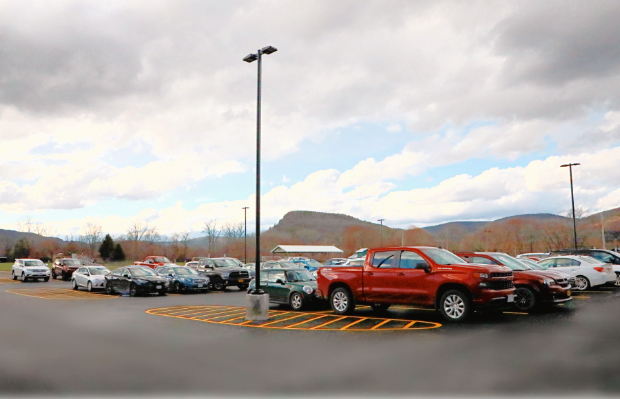 Parking lot filled with cars and trucks, light posts, on a cloudy day