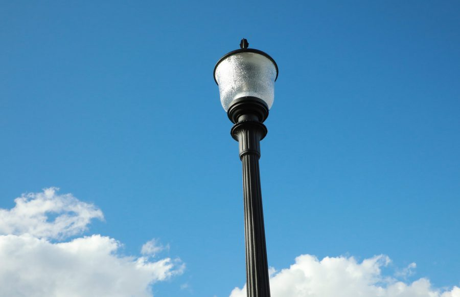 A lightpost and bright blue sky with fluffy clouds