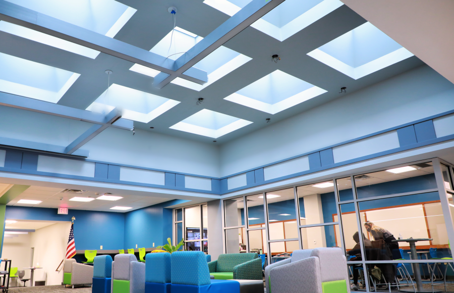 skylighting under colorful chairs with a glass encased classroom to the side