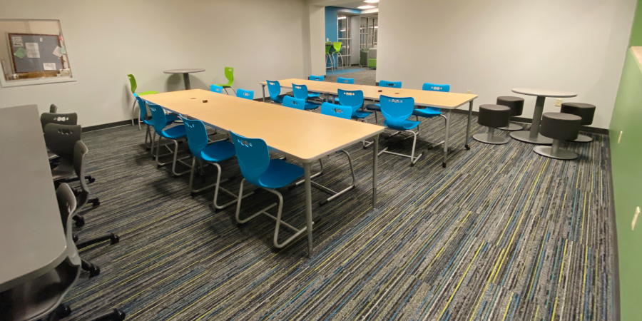 room off of library with different tables and chairs and window to tech department assistance