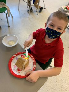 student looks up from spreading icing on gingerbread house