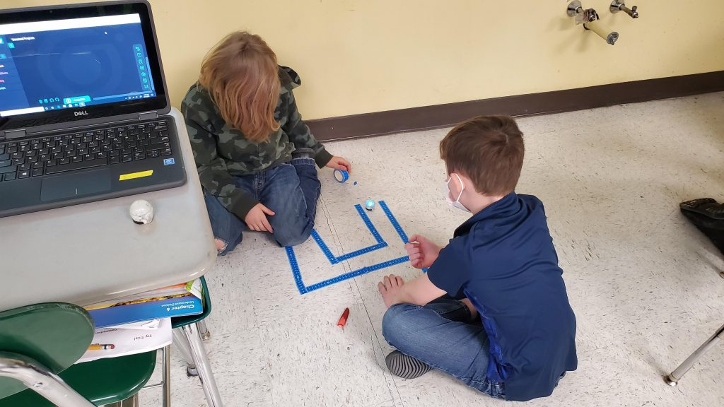 two students made a tape maze on the floor and are trying to get their robot to follow it