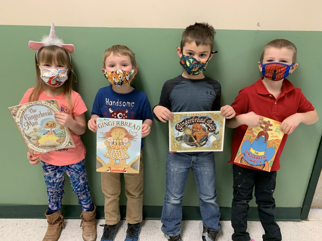 four kindergarted students each holding a book about gingermen
