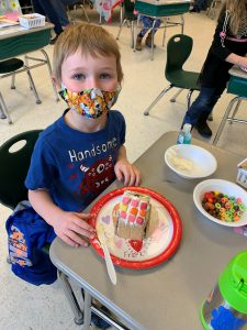 student looks up for picture while making gingerbread house