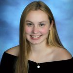 senior picture of girl with blonde hair wearing a black drape and smiling big with rosy cheeks