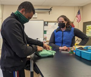 Student wraps a surgical pack with a vet watching.