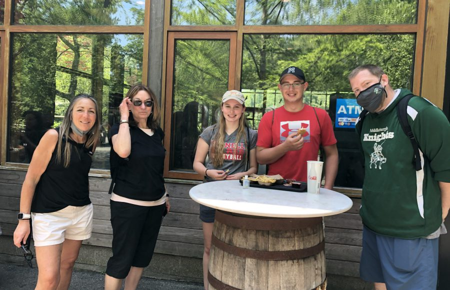 two students and three chaperones stand by a barrel table