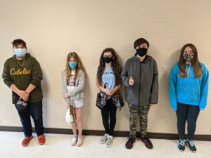 five students wearing face masks stand along a wall for a picture