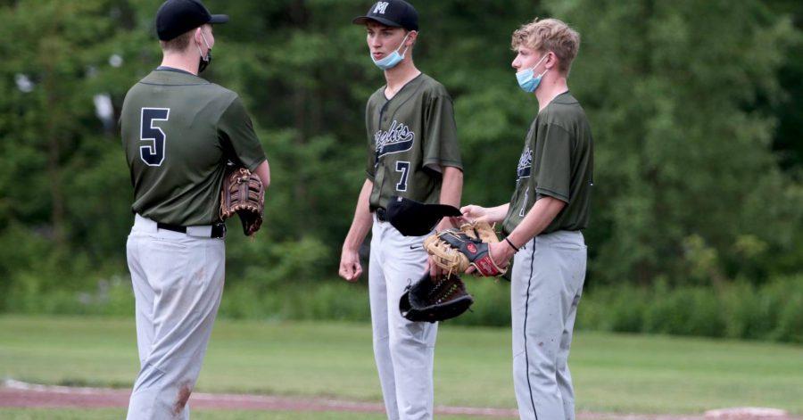 three baseball players on the field talking