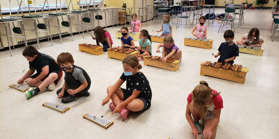 students sitting on the floor playing xylophones