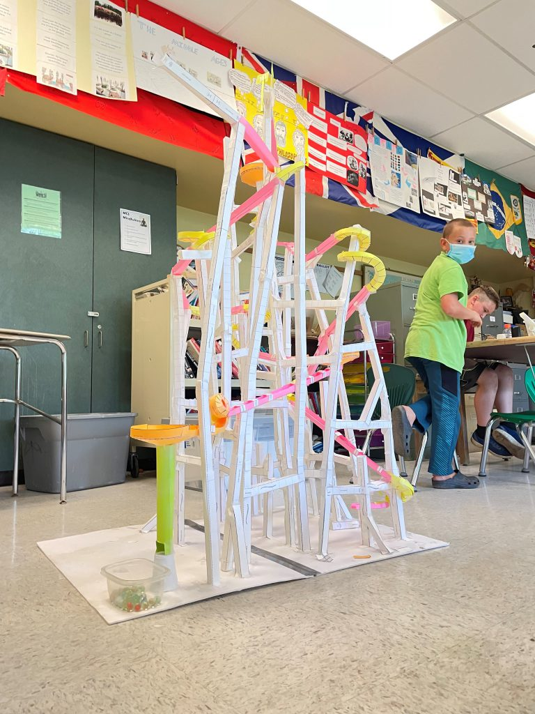 tall paper roller coaster and boy looking back at his creation