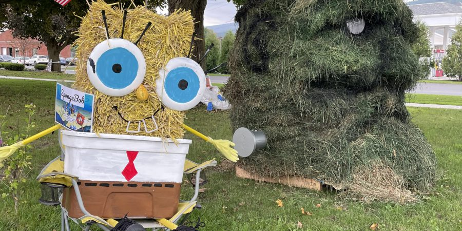 a scarecrow of SpongeBob Squarepants sitting on a chair next to a huge head of Frankenstein