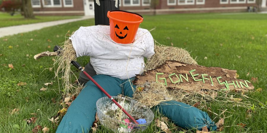 pumpkin head scarecrow sitting on grass, wearing jeans, holding a fishing pole that dips into a clear bowl with colored fish inside, a sign next to him says gone fishin'