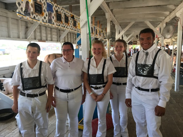 five FFA students, all wearing white, standing in a barn at a fair