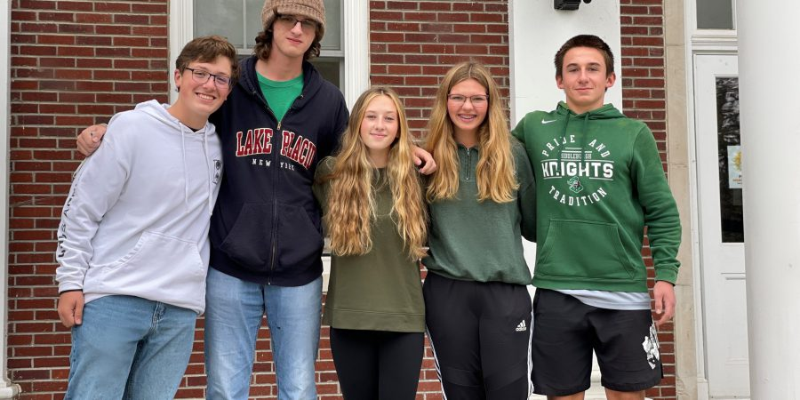 Five sophomores are standing up leaning into each other with their arms around each other outside on the steps of the high school
