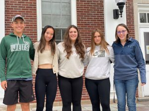 five seniors stand outside on the high school steps with their arms around each other
