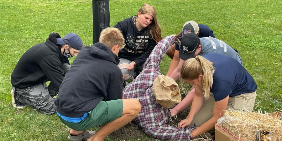 five students and a teacher are surrounding their scarecrow and stuffing it with hay