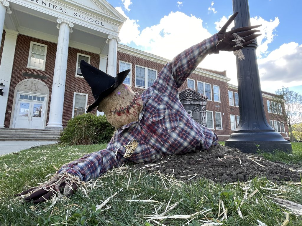 scarecrow with a flannel shirt and witches hat coming out of the ground and grave